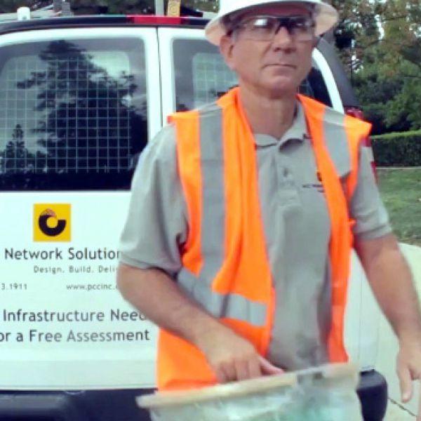 Man in orange vest working in the field.